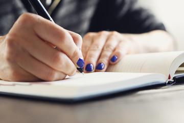Kalendarz firmowy. Kobieta zapisuje w kalendarzu notatkę