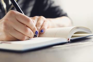 Kobieta pisze w kalendarzu. Kobieta zapisuje w kalendarzu notatkę