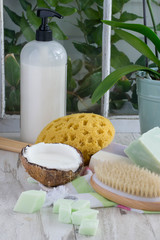 Indulge in skin care luxury with homemade soap and coconut milk body wash lotion, natural sea sponge and dry brush - vertical with room for text