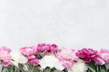 Peonies on bright gray concrete background with copy space. Wedding, gift, feminine cards, design or mockup projects. Desaturated effect