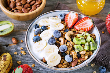 muesli bowl with sliced banana, blueberry, kiwi and strawberry on wooden table, closeup view. Healthy eating, dieting concept