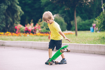 A little boy is riding a skateboard  in the park
