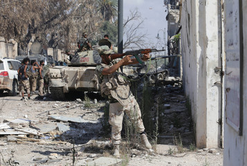 A member of Libyan National Army fires a weapon during clashes with Islamist militants in the militants' last stronghold in Benghazi