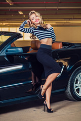 Sexy blonde pin up style girl sits in the car