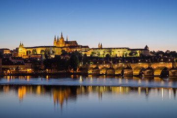 View of the lit Prague (Hradcany) Castle, Charles Bridge (Karluv most) and their reflections on the Vltava River in Prague, Czech Republic, at night.