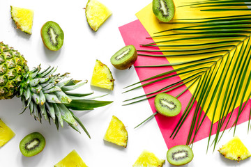Concept of summer tropical fruits. Pineapple, kiwi and palm branch on white background top view copyspace