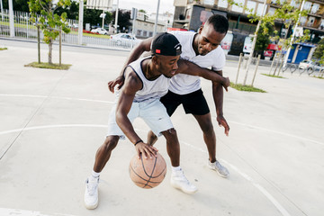 Young basketball players playing basketball on an outdoor court