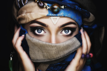 Portrait of young beautiful woman close up. Perfect makeup. Perfect skin. Fashion photo.Beauty lady with colored turban over blue background Wall mural