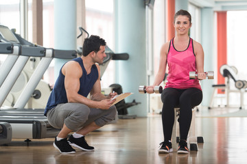 Personal Trainer Helping Woman On Biceps Exercise