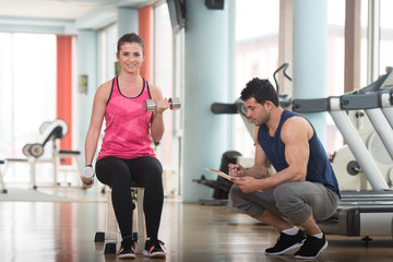 Gym Coach Helping Woman On Biceps Exercise