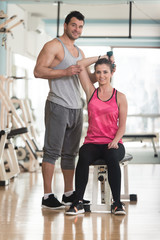 Personal Trainer Helping Woman On Triceps Exercise