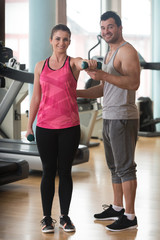 Gym Coach Helping Woman On Shoulder Exercise