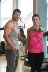 Personal Trainer Helping Woman On Shoulder Exercise