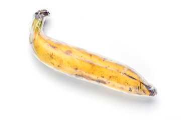 A ripe brown yellow banana is wrapped by preservative plastic film, food protection concept.