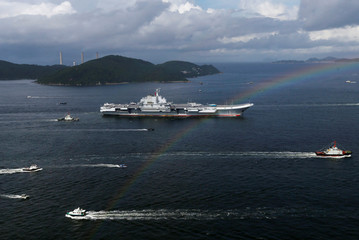 China's aircraft carrier Liaoning sails past a rainbow as it enters Hong Kong