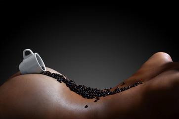 A photograph of a white cup of hot coffee with lots of coffee beans, which lies on a beautiful and sexy naked female body. Erotic photo about the use of coffee drinks