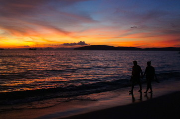 Silhouettes of a couple holding hands and walking on the beach during colorful sunset