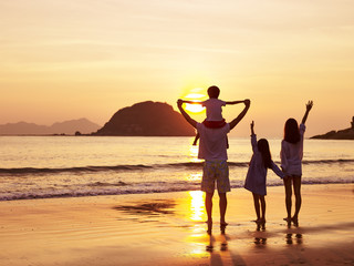 asian family watching sunrise or sunset on beach