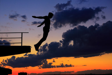 Man is jumping from edge of roof. Clouds and sunset