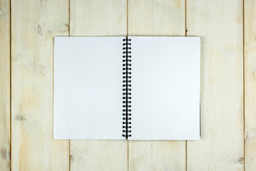 Top blank notebook on wooden table background.