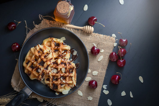 Honey on waffles with cherry berries on dark wooden background. breakfast concept