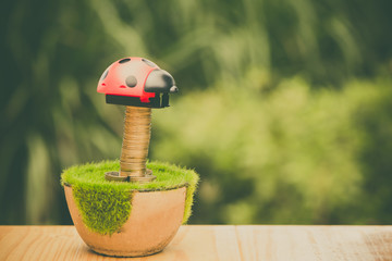 Stack of gold coin on artificial grass in pot, on wooden table with green nature background. vintage tone.