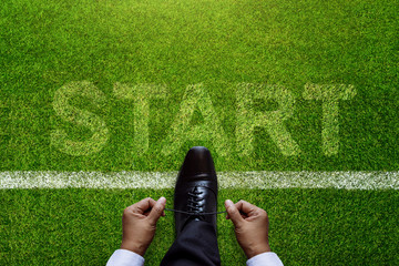 Top view of Businessman tie his shoes over Start line in soccer grass field with Start word background, Business Challenge or do something new concept