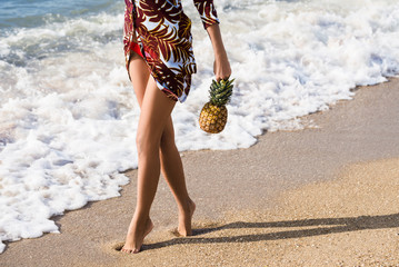 Sexy female legs on the beach and exotic fruits