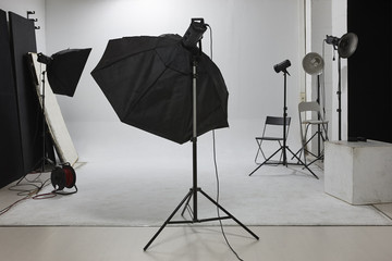 Professional photographic studio set with flashlights and white background.