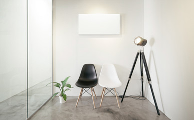 Empty office waiting room.Loft interior style , white canvas print on the center white wall. Two black and white chairs at the concrete floor .