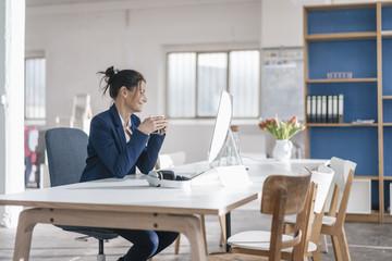 Businesswoman sitting at desk in a loft drinking coffee