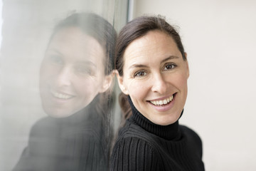 Reflection and portrait of smiling businesswoman wearing black turtleneck pullover