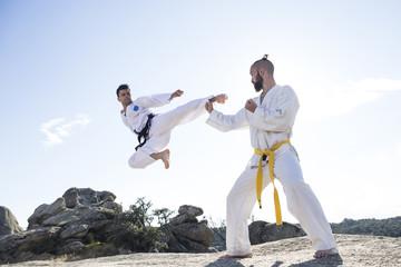Man doing a jump kick during a martial arts combat