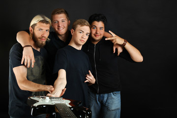 A musical group with guitars posing on a black background.