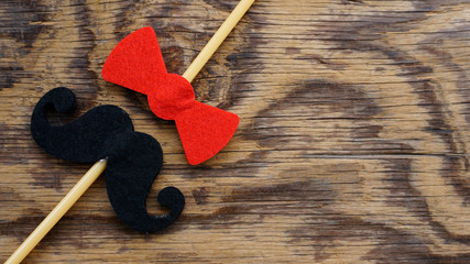 Top or flat lay view of Photo booth props a bow tie and a mustache  on a wooden background flat lay. Birthday parties and weddings.