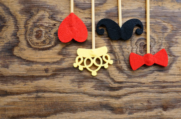Top or flat lay view of Photo booth props a heart shape, bow tie, mustache and a crown on a wooden background flat lay. Birthday parties and weddings.