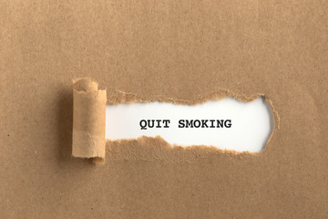The text QUIT SMOKING behind torn brown paper