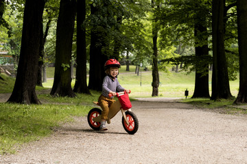 Fototapeta Boy riding on his bicycle in the park