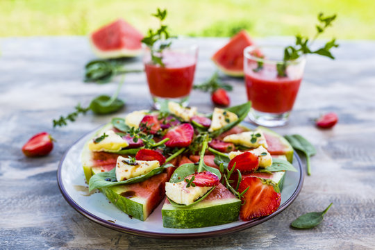 Delicious watermelon pizza with cheese and herbs on a table in the garden