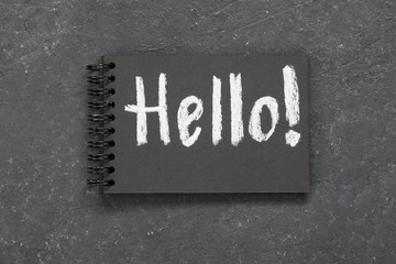An inscription hello written in white chalk on a black notepad on a black table.