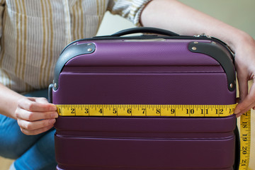 Close Up Of Woman Measuring Suitcase Before Holiday