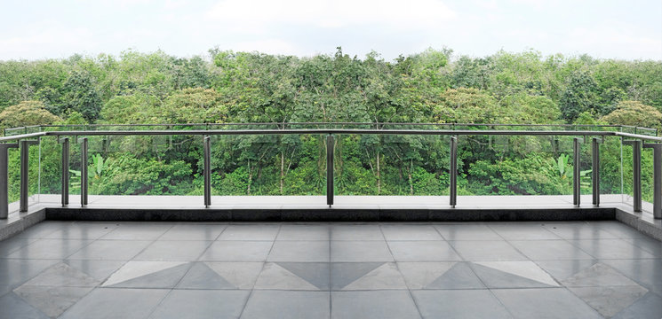 Panoramic view of a green forest canopy from a modern glass balcony.