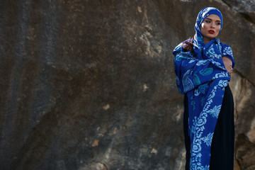 Gorgeous Young East Woman  portrait in hijab. Beauty Model Girl with bright eyebrows, perfect make-up.Traditional national clothes. In front of a mountain background