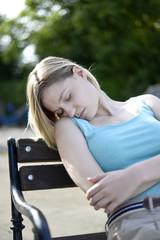 junge Frau schläft auf Bank