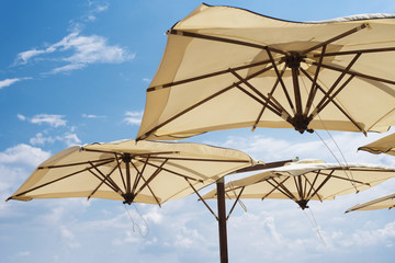 Large parasols. Beach season, time of rest and travel. Place for the text. Blue sky background. Beach umbrellas from the sun