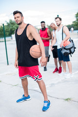 basketball player holding ball with multicultural team standing behind on court