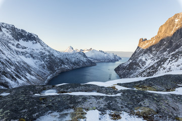 Top view of snowy peaks and frozen sea of the Ornfjorden surrounding the village of Fjordgard, Senja, Troms, Norway, Scandinavia, Europe