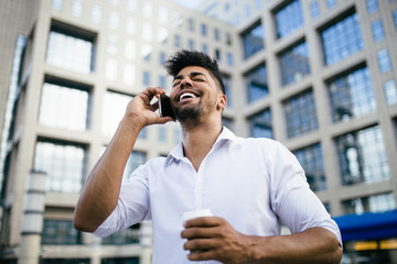 Young handsome Afro American man standing in front of huge modern business building smiling and talking on cell phone.