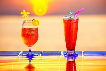 Colorful closeup image of tasty red cocktails st swimming pool golden sea sunset background.