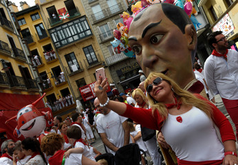 "A woman takes a picture in front of a ""cabezudo"" during San Fermin's ""Comparsa de gigantes y cabezudos"" in Pamplona"